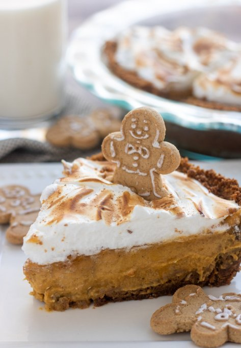A white square plate with a piece of pumpkin pie on it. The pie is topped with toasted maple meringue and a gingerbread cookie. There's a mini gingerbread cookie on the plate, a glass of milk in the background and a pie dish.