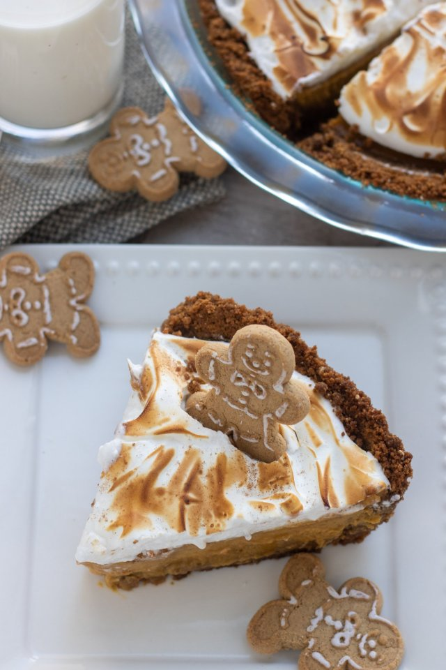 A slice of pumpkin meringue pie with mini gingerbread men on the plate.  The meringue is lightly toasted.  There's a glass of milk and a pie plate in the background.