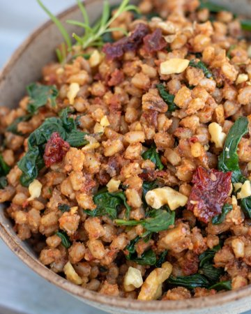 A brown speckled bowl filled with farro covered in sun-dried tomato pesto with fresh spinach and toasted walnuts.