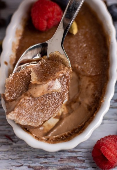 An oval ramekin with a spoonful of chocolate chai creme brulee. You can see the hardened caramelized sugar topping and the custard is creamy and chocolatey. There's a fresh raspberry in the background.