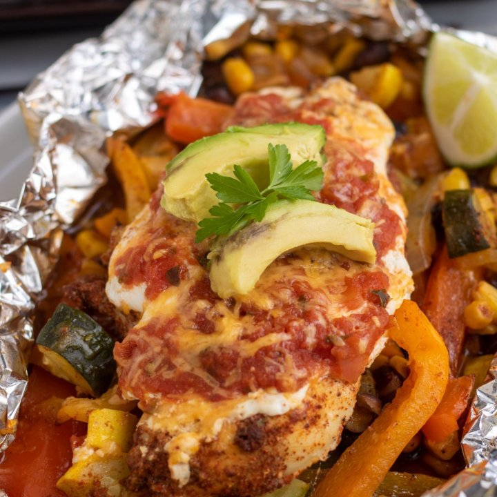 A foil packet filled with bell peppers, corn, black beans, onions, and zucchini topped with a piece of chicken breast that's got salsa, greek yogurt, avocado slices and cilantro on top of it.