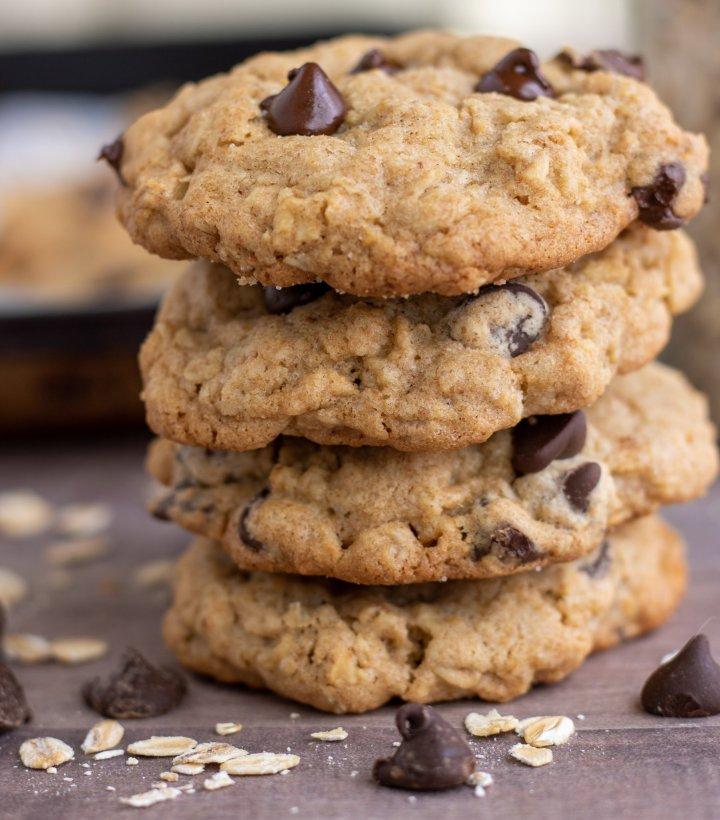Four oatmeal cookies stacked on top of each other. There's chocolate chips and rolled oats sprinkled around them with a baking sheet of cookies in the background.