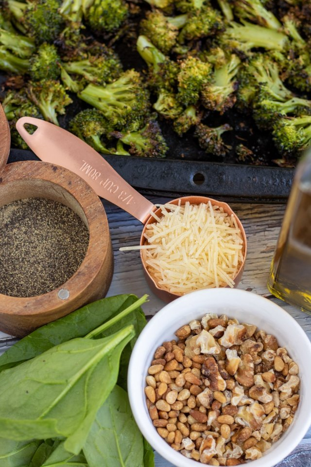 A small white bowl of toasted nuts, fresh spinach next to it, a copper measuring cup with Parmesan cheese, black pepper and a sheet pan of roasted broccoli florets in the background,