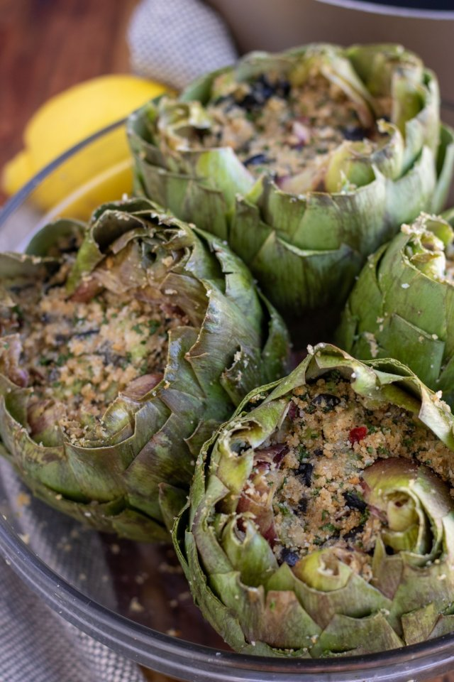 4 stuffed artichokes that have been prepared for cooking. There's a lemon and saucepan in the background