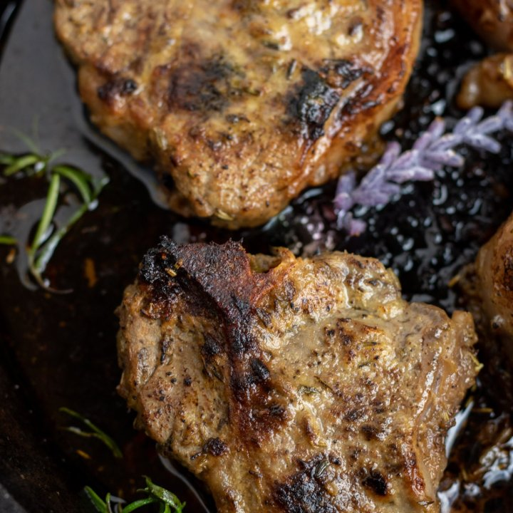 A cast iron pan with seared lamb chops baked in it. They're golden brown with fresh rosemary and lavender in the pan.