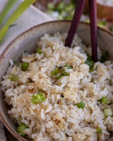 A brown speckled bowl filled with white rice that's slightly crispy and has scallions on top and sesame seeds. There's a pair of chopsticks sticking out of the bowl. There's a beige cloth napkin next to the bowl on a wooden surface with sliced scallions and white rice in the background