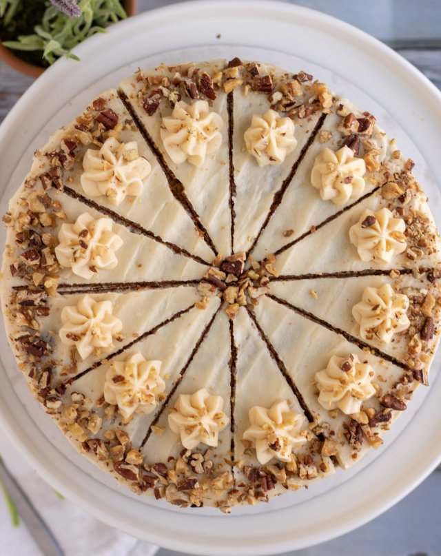 An overhead shot of a decorated carrot cake on a white cake stand. It's got crushed nuts sprinkled around the border and it's sliced into 12 equal slices. There's a lavender plant in the background.