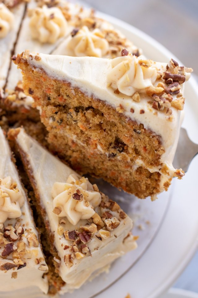 A homemade carrot cake with a slice being taken out of it on pie server. The cake has toasted nuts sprinkled on it and it's frosted with cream cheese.