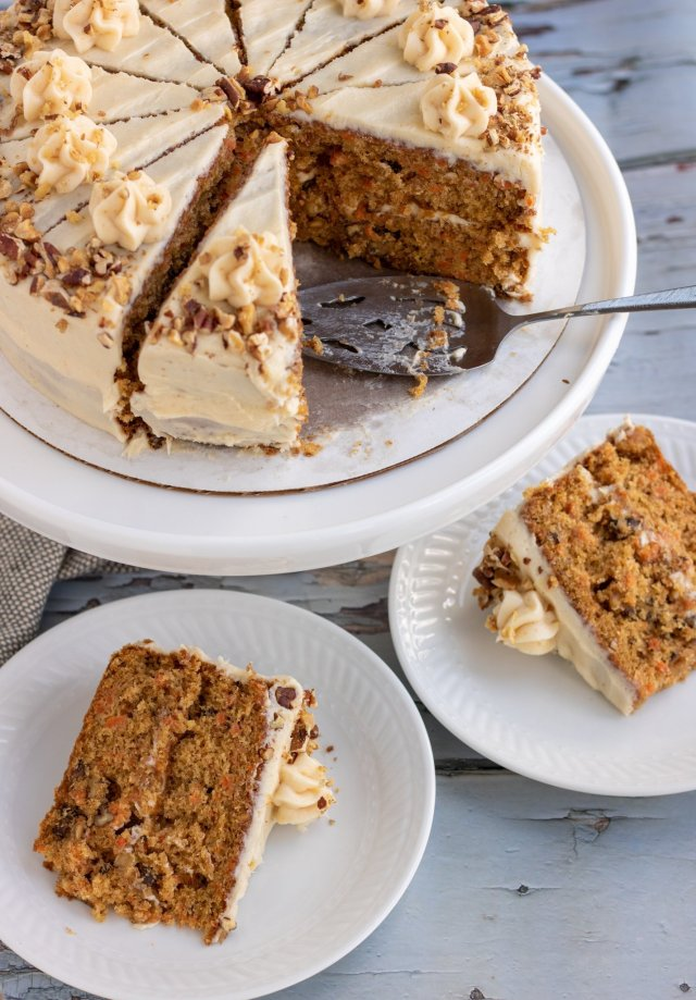 Carrot cake on a white cake stand with a pie server next to it. There's two small white plates with a piece of carrot cake on it.
