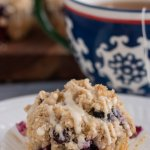 A small white plate topped with a blueberry muffin. The liner has been peeled off the muffin and it's topped with crumble topping with glaze dripping down it. You can see more muffins in the background on a wooden board and a blue and white swirled tea cup with a tea bag hanging out of it