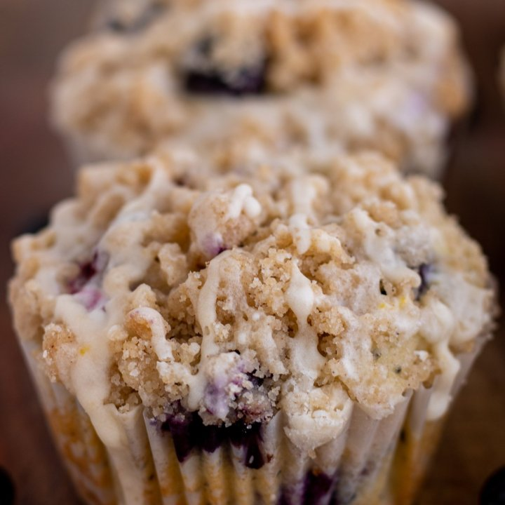 A blueberry crumble muffin on a wooden cutting board with glaze dripping down the side. There's a fresh blueberry next to the muffin.
