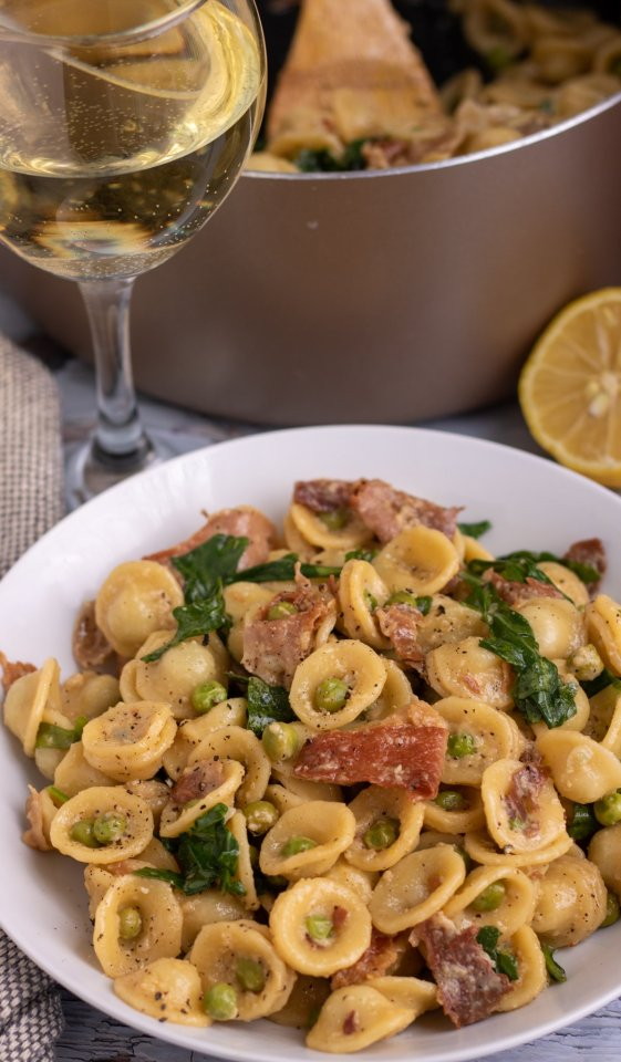 A white pasta bowl filled with orecchiette pasta, peas and prosciutto. There's a gold large saucepan in the background with more pasta and a glass of wine in the background.