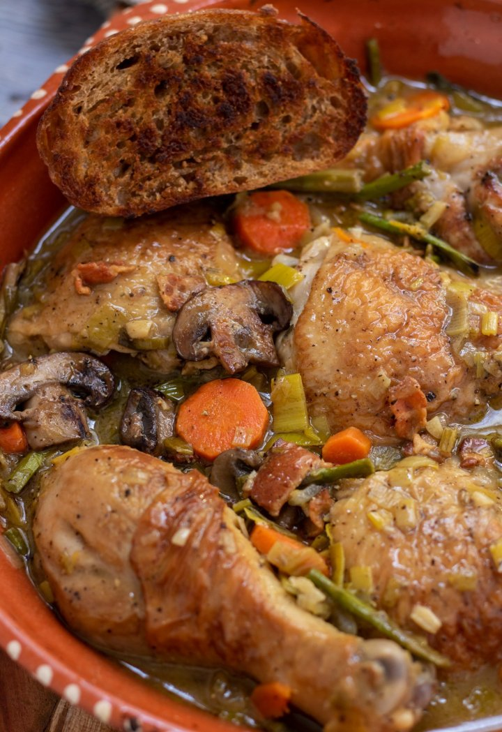 A round rustic casserole dish with coq au vin blanc with carrots, mushrooms, asparagus and leeks. There's a piece of crusty golden bread on the edge of the dish and the chicken skin is golden brown