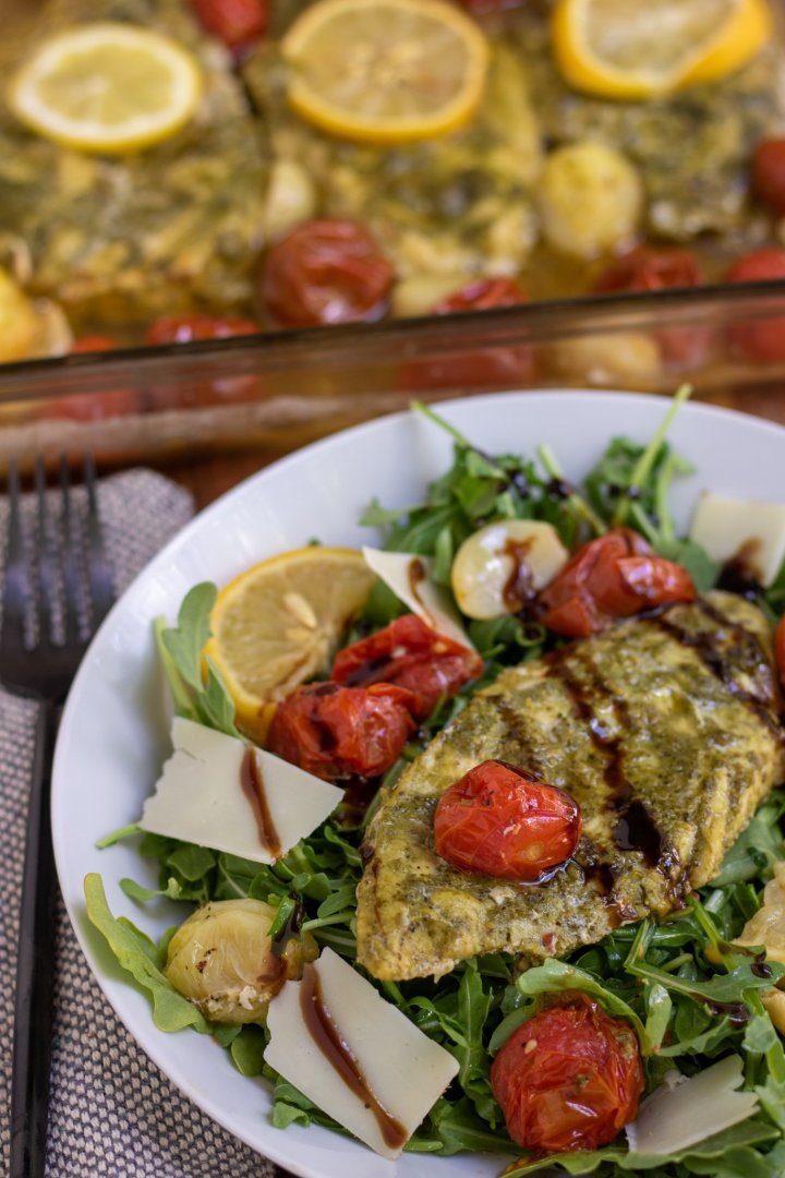 A white pasta dish filled with arugula and topped with pesto chicken. There's shaved Parmesan cheese and a fresh lemon wedge on the dish. It's drizzled with balsamic glaze. You can see a glass baking dish filled with chicken and tomatoes in the background.