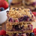 A wooden surface topped with 3 stacked berry oatmeal crumble bars with blueberries and raspberries sprinkled around them.