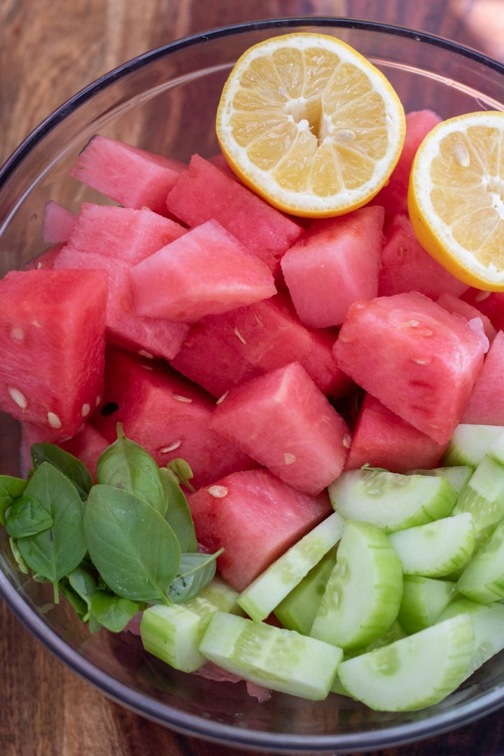 A large glass bowl filled with cubed watermelon, sliced cucumbers, fresh basil leavevs and lemons.