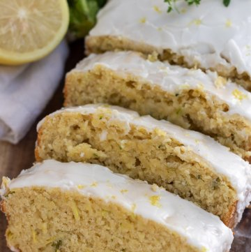A wooden background with a loaf of lemon glazed zucchini bread that's sliced into 3 slices. There's a sprig of fresh thyme on top of the loaf with a half a lemon and zucchini in the background
