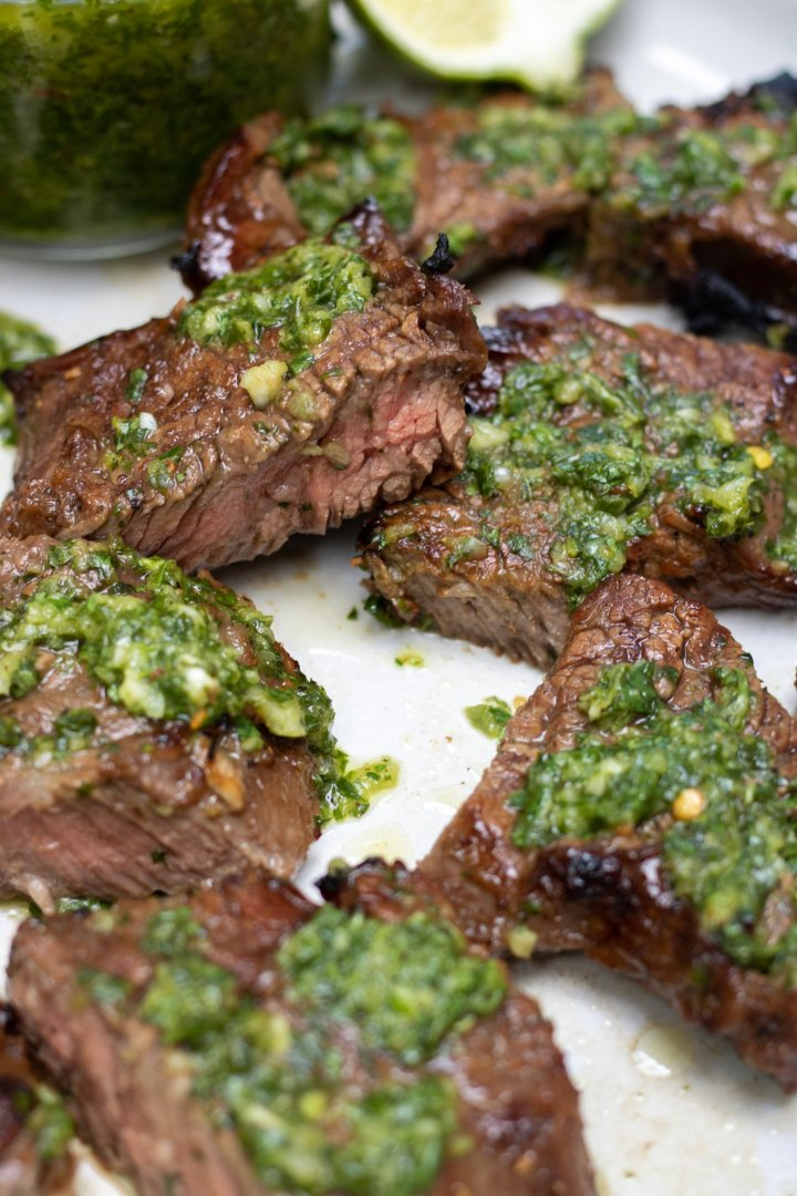 Bite sized pieces of grilled steak tips that are topped with chimichurri sauce. One of the steak tips are cut in half and you can see it is cooked medium rare.