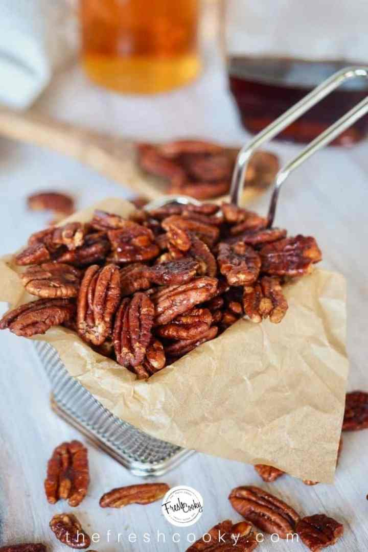 Candied pecans with bourbon and maple on brown parchment paper.  There's a wooden spoon in the background.
