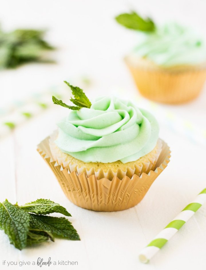 A mint julep cupcake with a gold cupcake liner and topped with fresh mint leaves.  There's a green and white striped straw, another cupcake and fresh mint leaves in the background