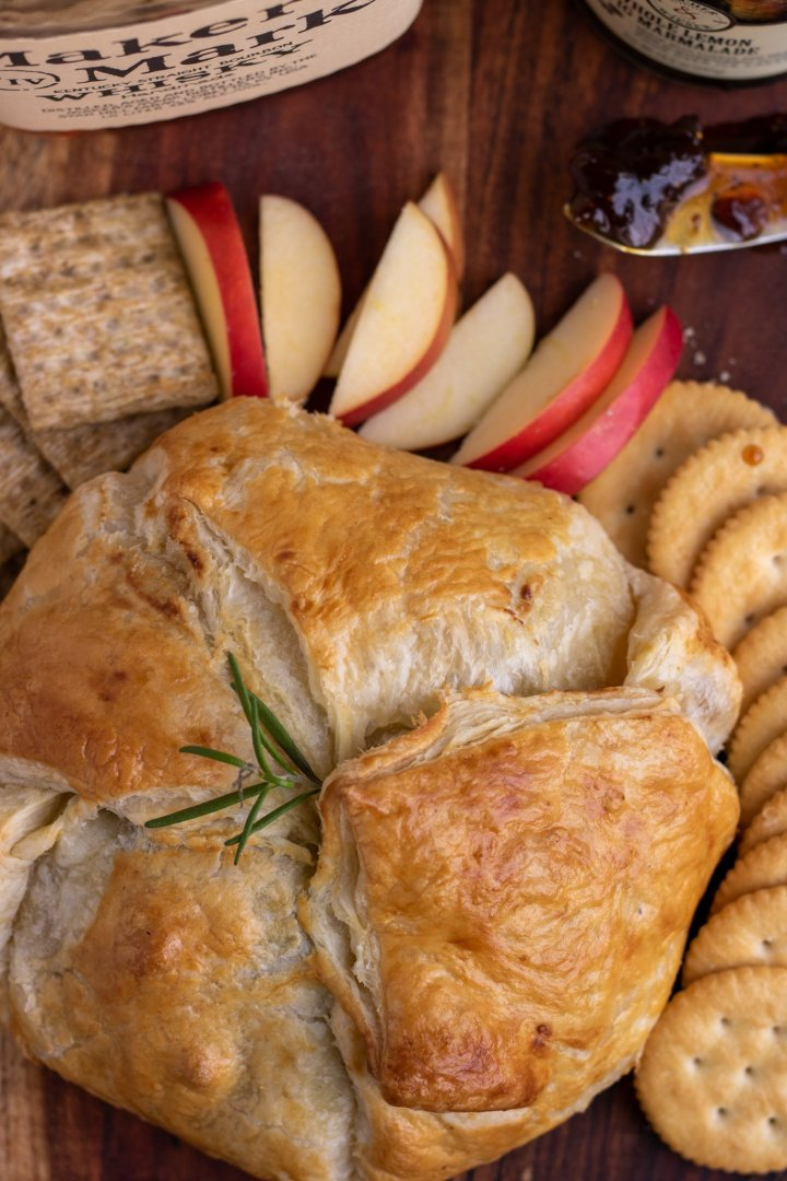 A wooden background with a baked brie wrapped in puff pastry on it. The pastry is golden brown and topped with a fresh rosemary sprig. There's crackers and red apple slices arranged around the brie. You can see a spreading knife in the background with fig jam on it