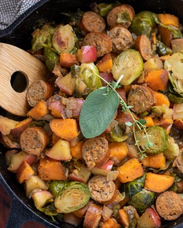 A cast iron skillet filled with chicken sausage, apple and veggies. It's got a wooden serving spoon in it and it's topped with a fresh sage leaf and thyme sprig