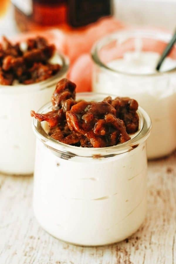 A small glass jar filled with no bake cheesecake that's topped with bourbon candied bacon.
