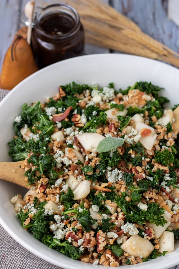a large white serving bowl filled with kale and farro salad. It's got a fresh sage leaf on top and two wooden serving utensils in the salad. The small glass jar of balsamic fig dressing is in the background with a whole pear and dried wheat stalks.