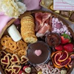 a charcuterie board filled with fruits, cheese, valentine's candies and chocolates. There's a white flower in the background with a box of chocolates