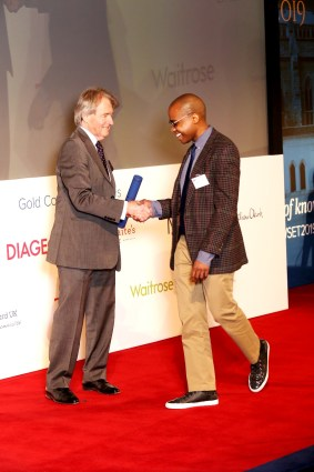 British wine expert, Steven Spurrier, who organized the Judgement of Paris 1976 winetasting, awards Reggie Solomon a DipWSET diploma in Guild Hall in London.