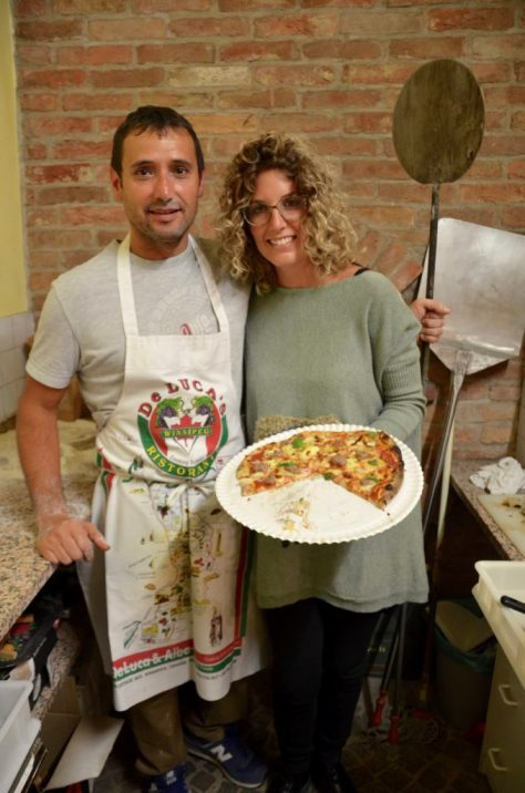 Giorgio Faccenda, with the aid of his wife Cristina Deltetto, keeps the supply of pizzas going on Christmas Eve in the Deltetto winery's tasting room.