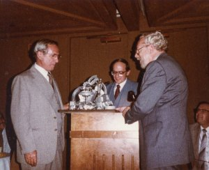 Meo being presented with metal alloy from fellow engineers during his retirement from Rocketdyne, 1983