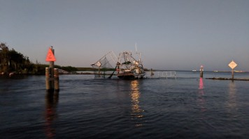 Shrimp boat sitting between the river and lake collecting shrimp as they go through then narrow, with http://bayoubadboysbowfishing.com/ in the bayou outside of Lafitte, LA