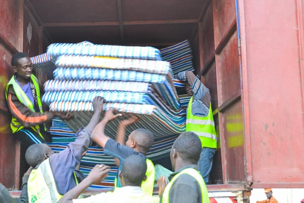 A group of mean in neon green vests work to unload a truck filled with mattresses