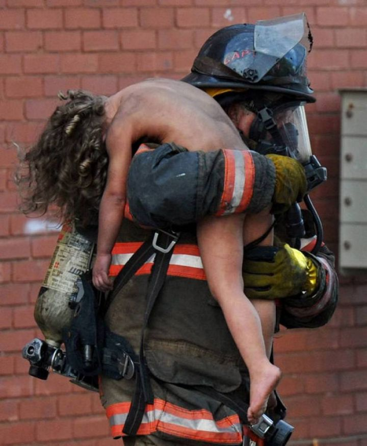 29 Powerful Pictures - Captain Donald Spindler saves 6-year-old Aaliyah Frazier from a fire in Indiana.