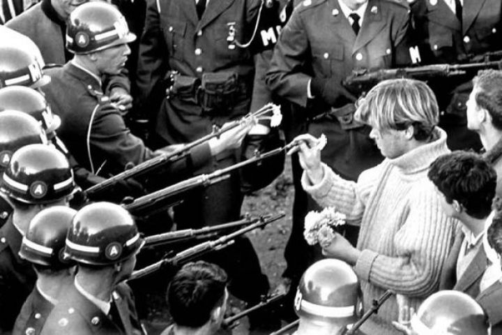 29 Powerful Pictures - A Vietnam War protester inserting flowers into National Guardsmen's rifle barrels.