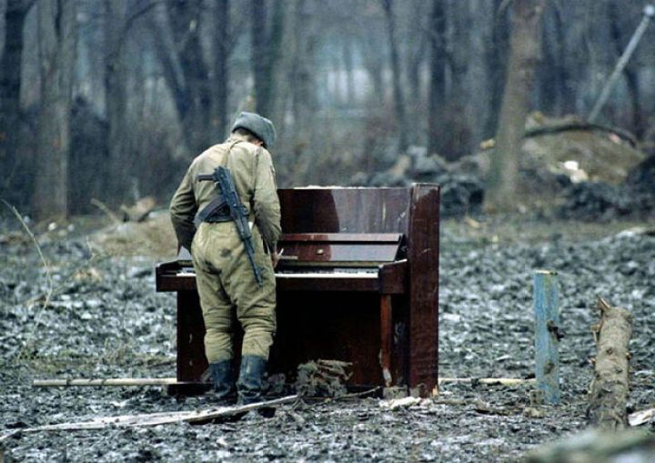 29 Powerful Pictures - In 1994, a Russian soldier plays an abandoned piano in Chechnya.