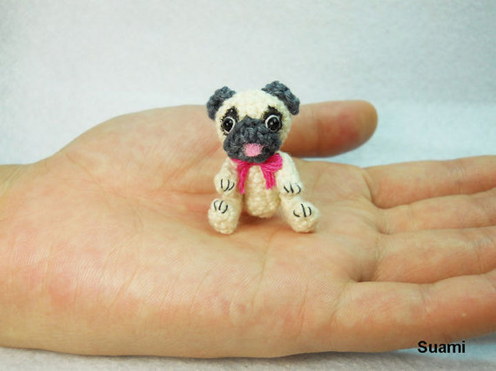 Tiny crochet Pug with a pink bow.