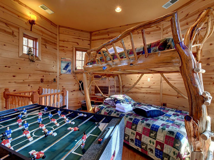 This kid's room features custom log bunk beds and a foosball table. There is also a door leading outside or a fun ladder (see picture above) that leads you to the second floor.