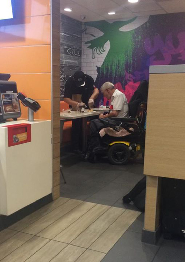 An employee of McDonald's helping a disabled elderly man eat his meal.