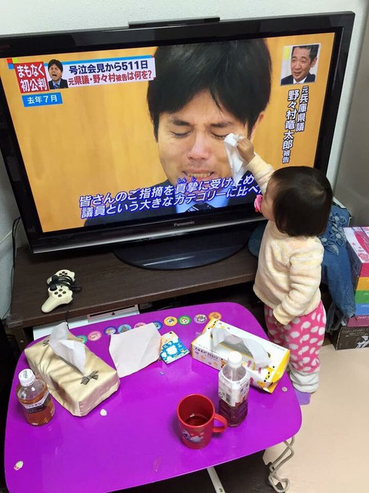 A toddler wiping away tears from a man crying on television.