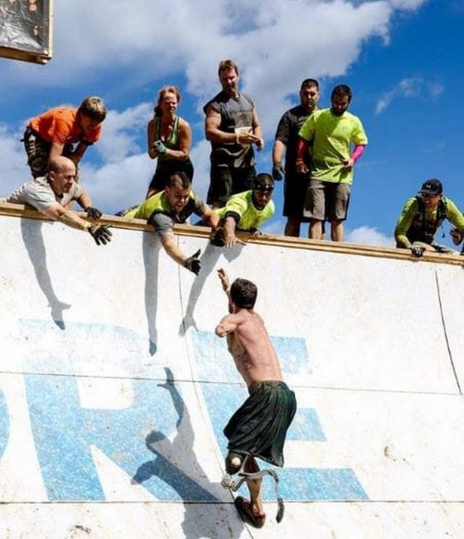 Double-amputee Iraq veteran 10 miles into the Tough Mudder competition and getting a helping hand from fellow competitors.
