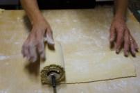 Mariuca rolling the dough onto the wheel for the ravioli machine