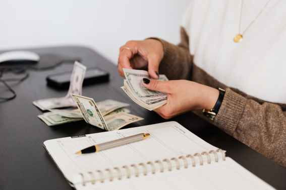 crop payroll clerk counting money while sitting at table; photo from Win's Books Author Spotlight guidelines