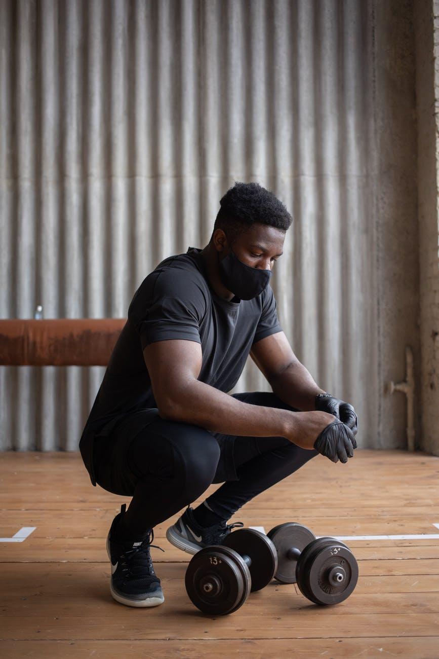 black sportsman in mask putting on gloves near dumbbells; the jock; stock character