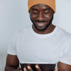 man in white crew neck t shirt holding black smartphone