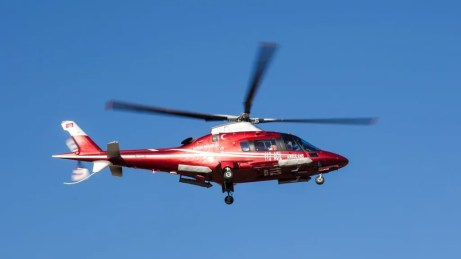 flying red and white helicopter