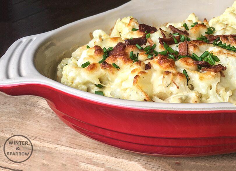 10-Minute Keto Cauliflower Au Gratin | winterandsparrow.com (Picture of cauliflower in a casserole dish topped with bacon and dill) #ketorecipe #ketorecipes #easyketorecipes #ketocauliflower