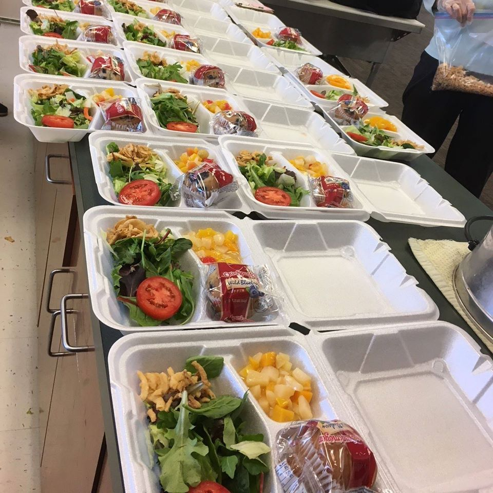 table full of pre-made lunch salads in styrofoam containers