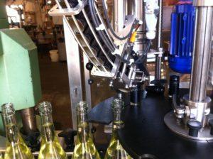 In Reih und Glied aufgereit werden unsere Flaschen mit Schraubverschlüssen bestückt